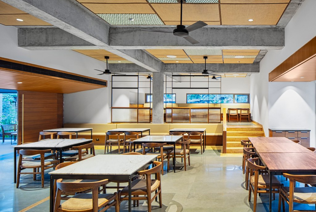 Architecture studio Hundredhands designed Bangalore International Centre in India. A cavernous auditorium lined with angled, perforated wooden panels sits at the heart of the cultural centre. The CAFE is casual and warm with Windmill ASANA model in Matt Black adorning the ceiling